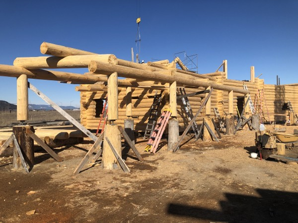 A handcrafted log breezeway leads to the log home under construction.