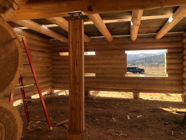 The interior of a full scribe log home under construction showing a stringer log and loft logs.
