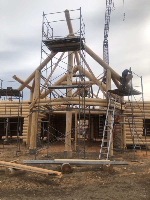 A Scandinavian full scribe log home under construction. The great room bay is a story and half tall with log columns.