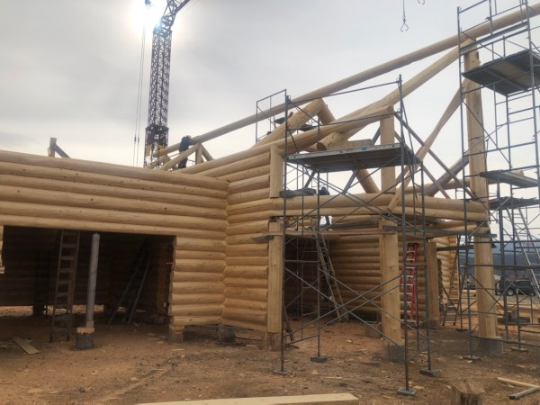 A handcrafted log home under construction with log trusses and large great room bay.