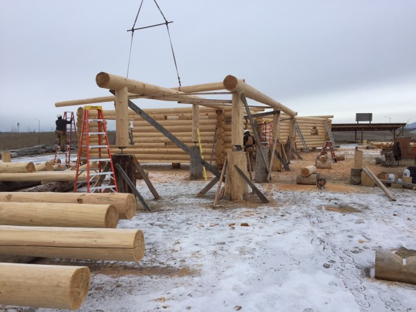 A tower crane moves the next log into place to be scribed and fitted in the shell of this handcrafted log home.