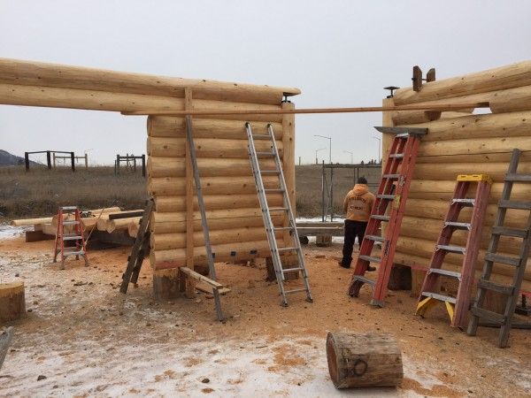 Handcrafted log walls stop at vertical columns which form the entry to a gazebo that will be built next.