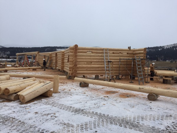 Employees scan the log bunks to select the right log for the next course in building this handcrafted log home.