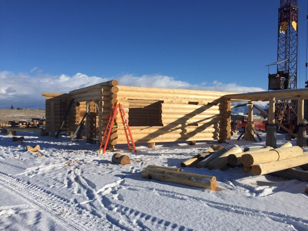 Fresh snow doesn't stop the building of this handcrafted log home.