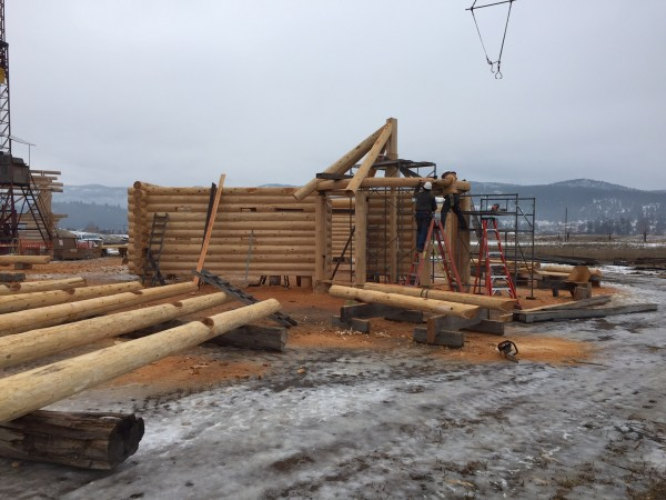Two employees setting a log course in place for the custom log gazebo.