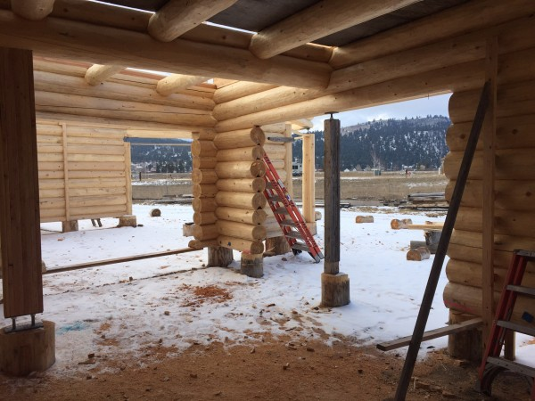 The interior of this Scandianvian full scribe log home shows the stringer logs, joists, and infill logs for the loft floor.