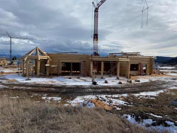 A handcrafted log home sits in front of the tower crane used for its construction.