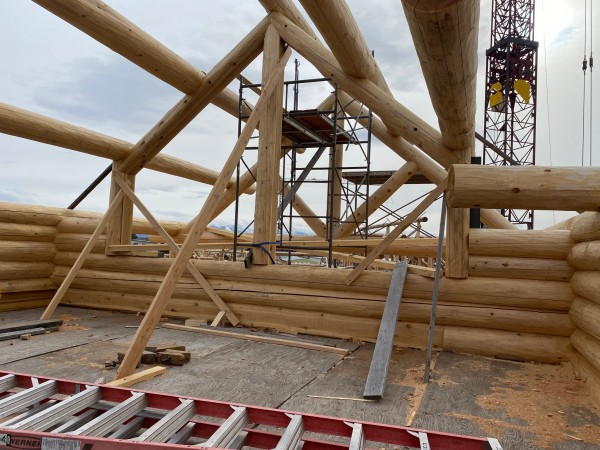 Handcrafted log home under construction showing the slotting and notching for the second level floor buildup.