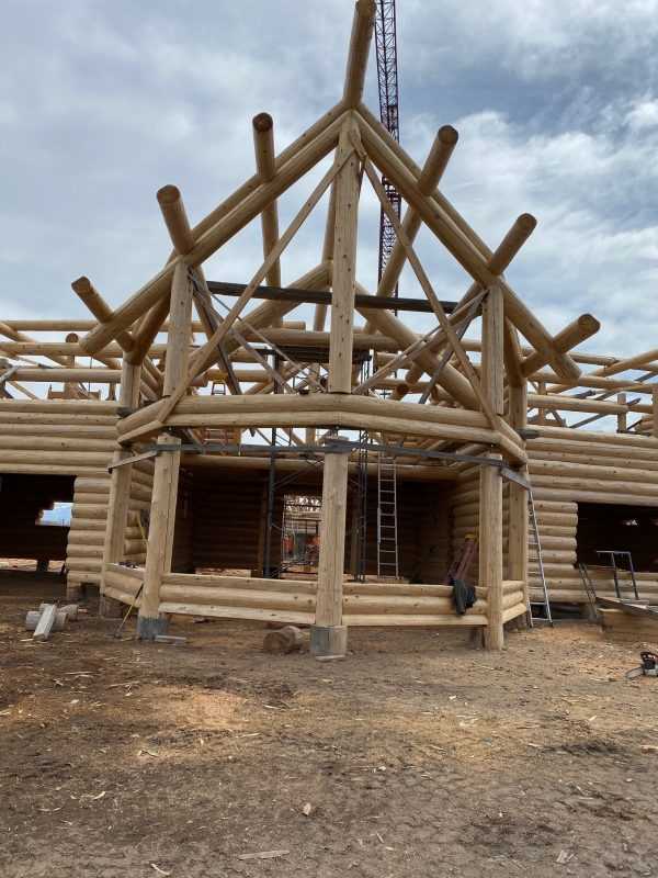 This full scribe log package has excellent example of log fly rafters and log columns to support the purlins and ridge.