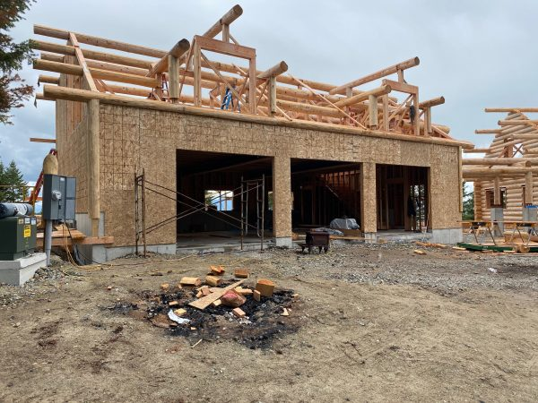A stick frame garage with a log roof system awaiting the log siding.