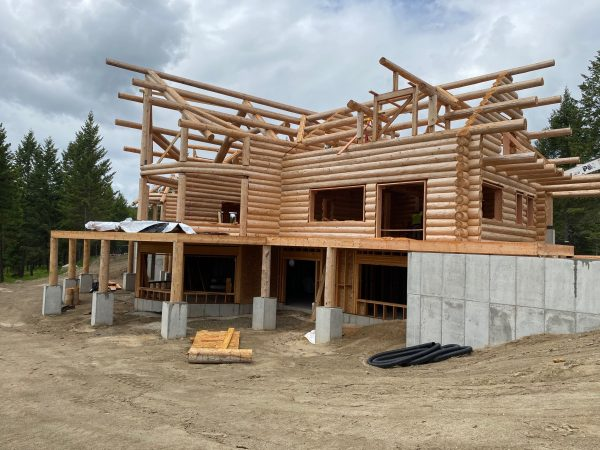 Window and door openings are being prepared to allow for settling in this custom log home.
