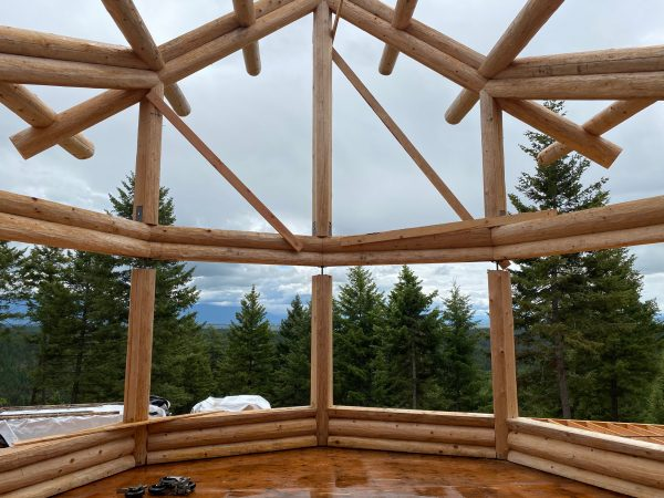 The homeowners will enjoy the view through the massive windows of the great room bay in this log home.