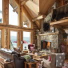 Log home living room with stone fireplace and cozy couch