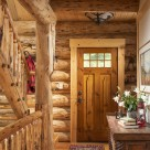 Interior of log home entry door with red runner carpet and log rails on log staircase