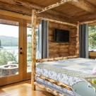 Log home bedroom with log bedframe and view to firepit and lake