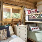 Log home bedroom with log bunkbed and custom quilts