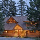 Twilight photo of handcrafted log home entry