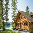 A handcrafted log home with full log gable end and red window trim with trees and lake in background