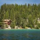 Handcrafted custom log home on a lakeshore surrounded by pine trees.