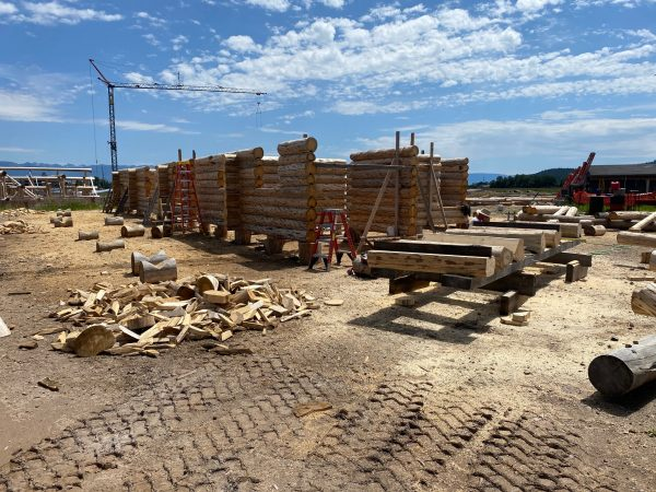 Log column are being fit with angle iron to form the connection between the horizontal log wall and vertical log column.
