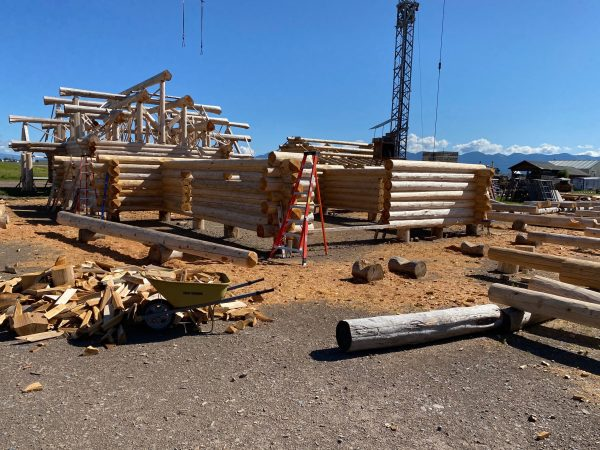 A completed log package with flared butt cedar logs sits in the background of a log package under construction.