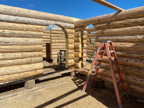 Two intersecting walls with matching arches create a unique look in this custom handcrafted log package.