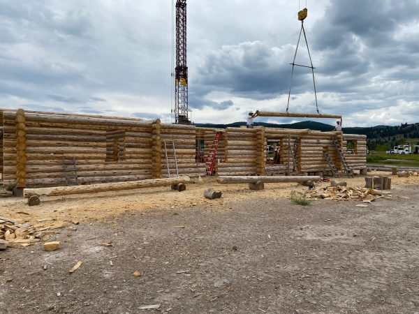 A tower crane with tongs and a spreader bar assembly make guiding the full length logs much easier and safer when building custom log homes.