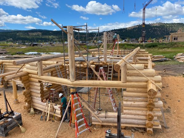 The first log purlins are set for the roof of this log home.