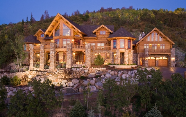 Stone and hand carved log work make a stunning image of this handcrafted log home.